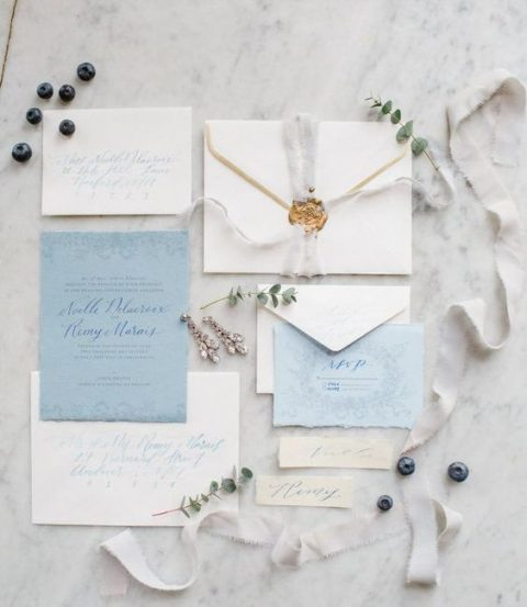 neutral and light blue wedding stationery with dove grey ribbons, seals and a raw edge