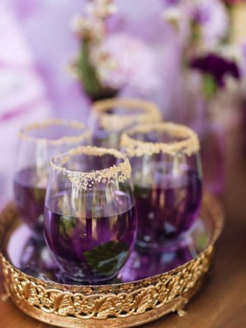ultra violet signature drinks with mint in gold rim glasses