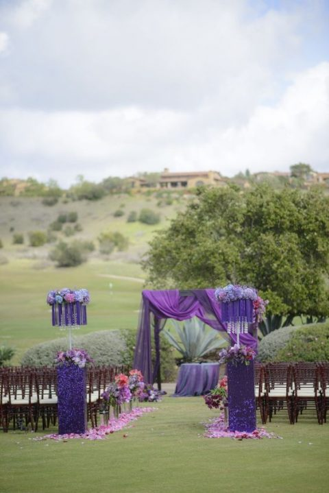 ultra violet stands with blooms and a purple and dip violet wedding arch