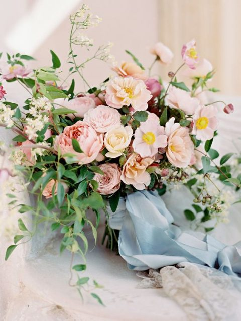 a blush and mauve wedding bouquet with blue ribbons