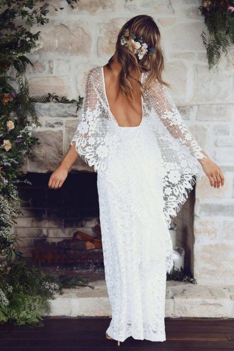 a boho lace wedding dress with a low back and large bell sleeves