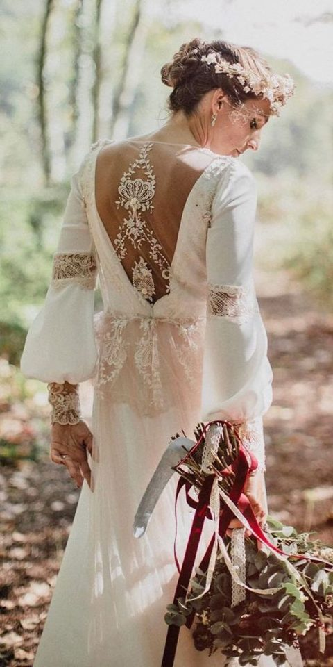 A Boho Wedding Gown With Bell Sleeves Lace Appliques And An Illusion Back