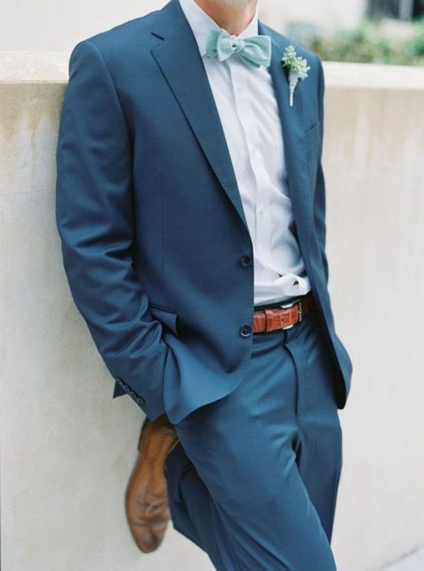 a bold blue suit with a white shirt, a mint bow tie and brown shoes