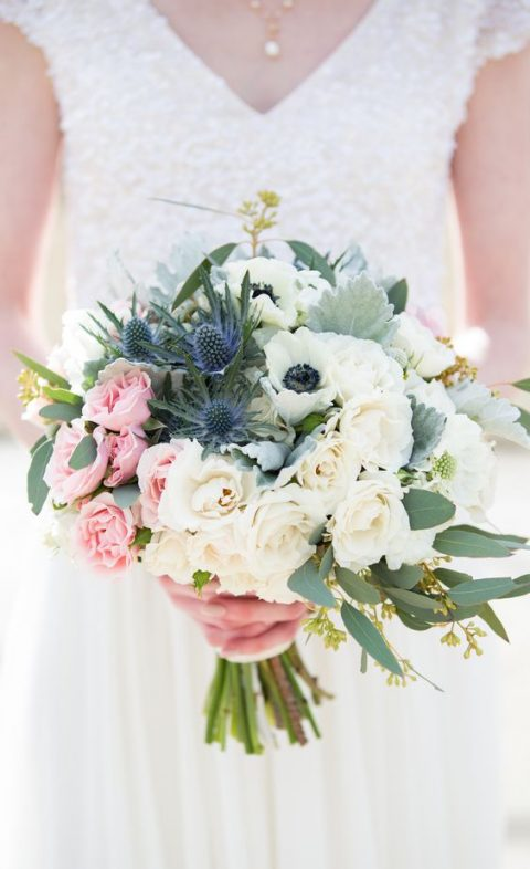 a bouquet with neutral roses, anemones, blush blooms and blue thistles