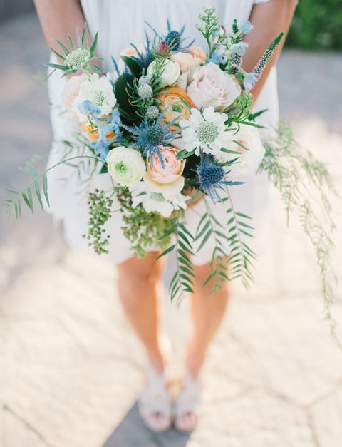 a cream, peachy orange and blue wedidng bouquet with greenery