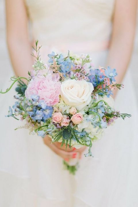 a fresh spring wedding bouquet with pink and blue flowers