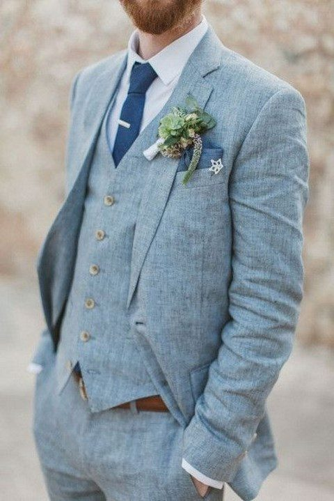a light blue linen three-piece suit with a bold blue tie