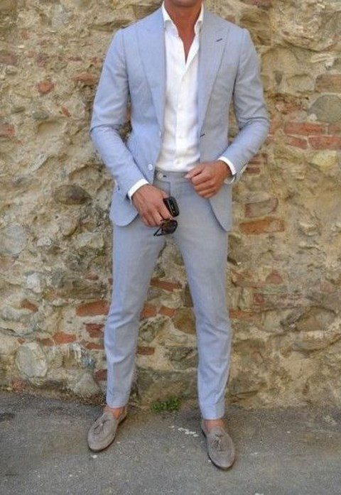 a light blue suit, a white shirt and grey moccasins