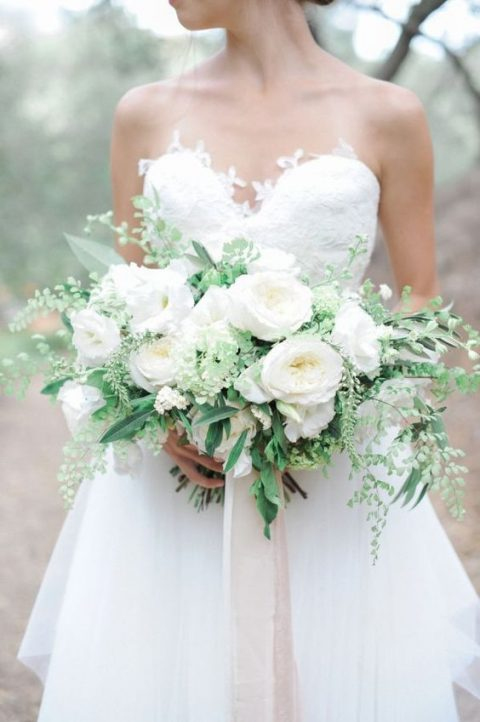 a lush wedding bouquet of greenery and white blooms with ribbons