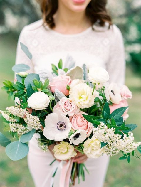 a lush wedding bouquet with blush and neutral blooms and lush greenery