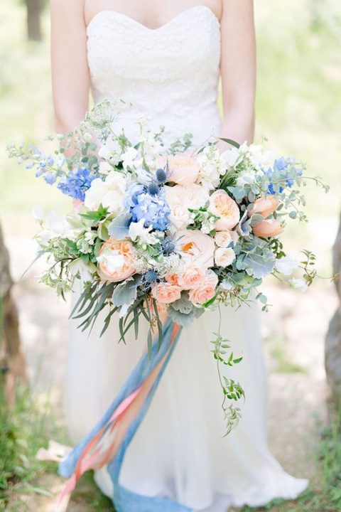 a lush wedding bouquet with peachy pink and blue flowers
