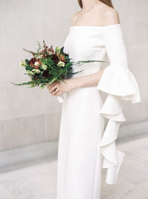 a modern off the shoulder wedding dress with a long ruffled bell sleeve looks chic