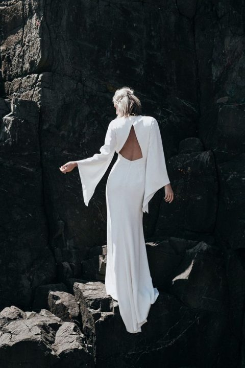 a modern wedding dress with bell sleeves and a triangle cutout back by Prea James