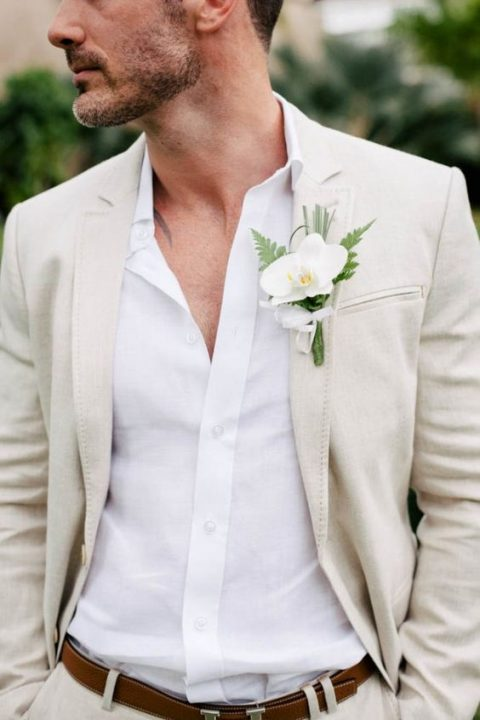 a neutral suit with a white shirt and an orchid boutonniere