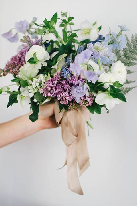 a purple and blue wedding bouquet with cream blooms and greenery