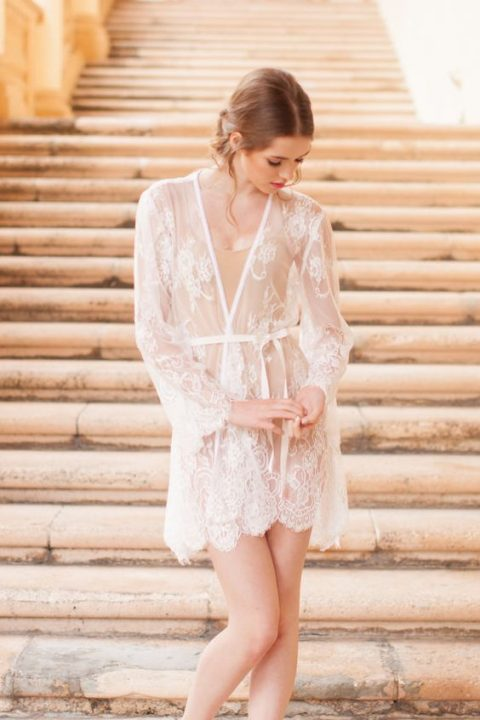 a sheer bridal robe with lace appliques on a nude top