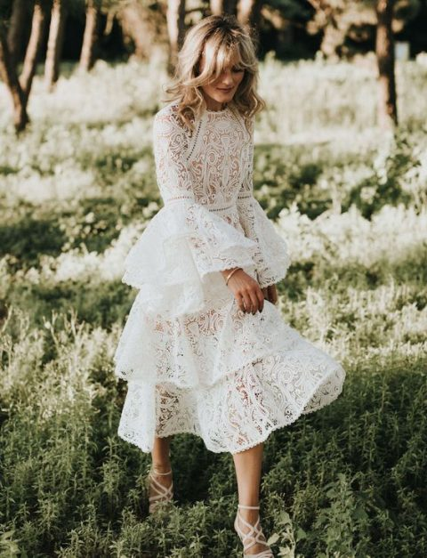 a summer lace wedding gown with a high neckline, bell sleeves and a ruffled skirt