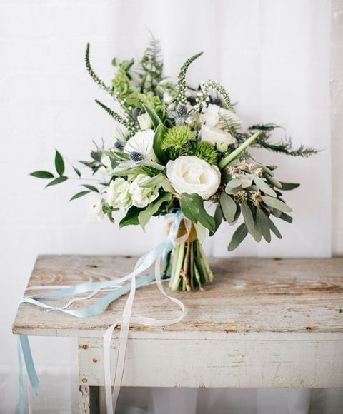 a textural wedding bouquet of white blooms and greenery with ribbons