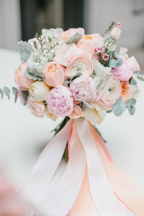 coral and pink wedding bouquet with pale eucalyptus and ribbons