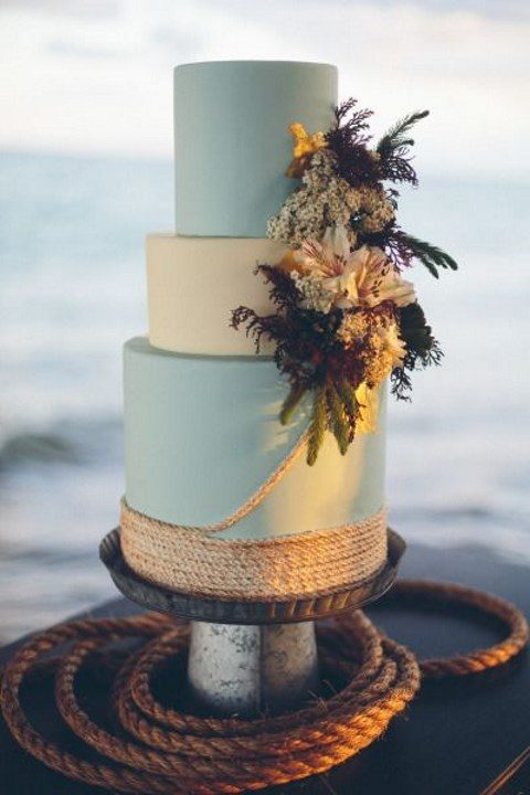a blue and white wedding cake decorated with rope and fresh textural blooms