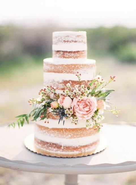 a chic naked wedding cake with fresh blooms and greenery