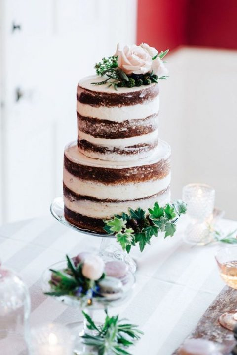 a chocolate naked cake topped with blush roses, blackberries and greenery