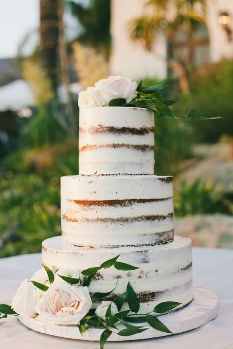 a chocolate naked wedding cake with blush blooms and greenery