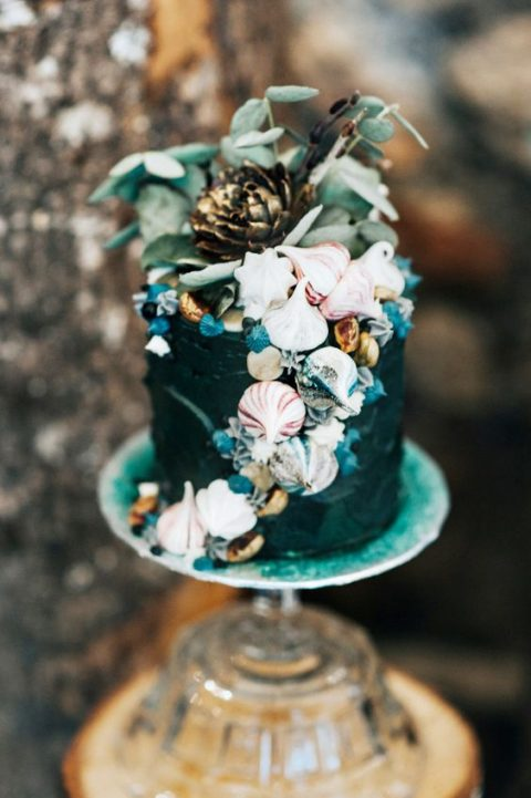 a dark teal wedding cake with fresh greenery, shells and candies for a mermaid feel
