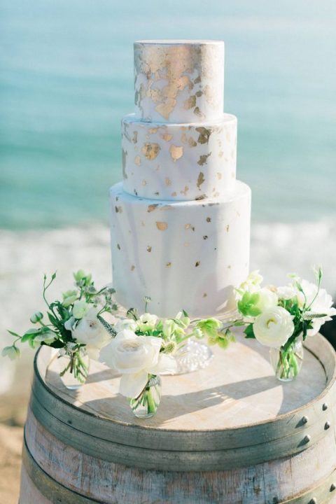 a light blue wedding cake with gold leaf is an elegant solution