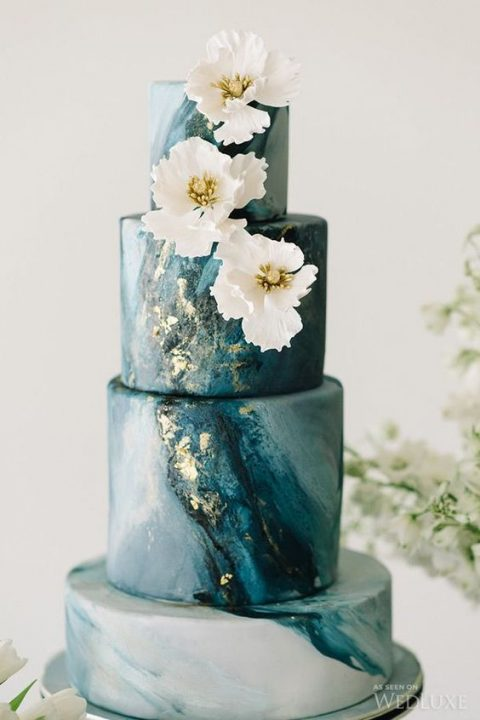 a marble beach wedding cake in blue shades with gold leaf and sugar flowers