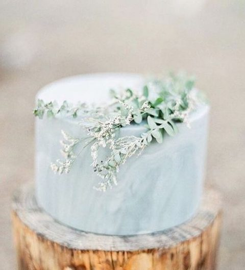 a marble grey blue wedding cake with some fresh greenery on top