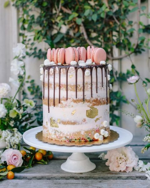 a naked cake with chocolate drip, meringues, pink macarons and gold leaf