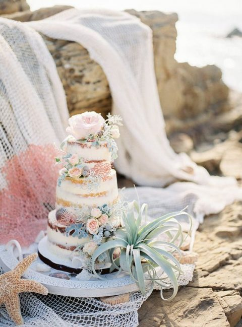 a naked wedding cake topped with fresh blooms, shells, air plants and leaves