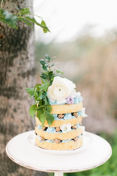 a naked wedding cake with blue cream, gilded blackberries and blooms on top