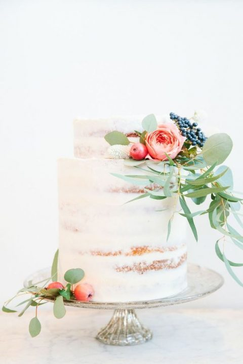 a naked wedding cake with fruits and blooms plus fresh greenery