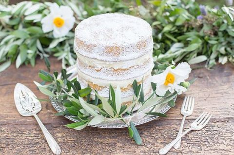 a naked wedding cake with powdered sugar and fresh greenery