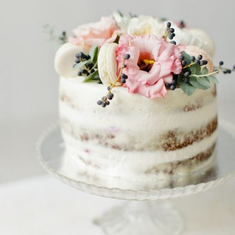 a naked wedding cake with vanilla macarons, berries and pink blooms