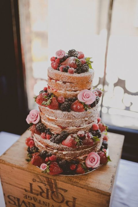 a pretty naked wedding cake with berries and pink roses and sugar powder on top