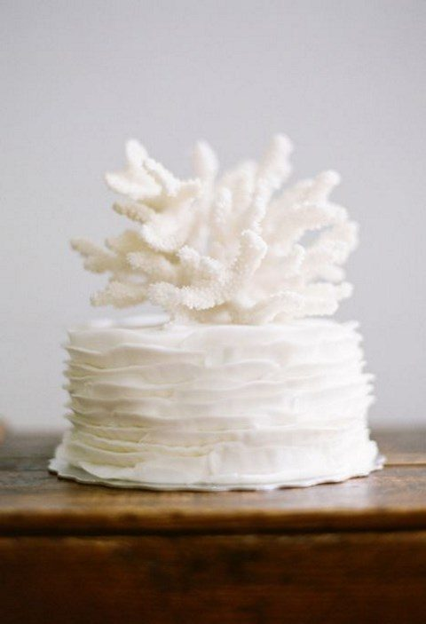 a pure white textural wedding cake with a coral on top