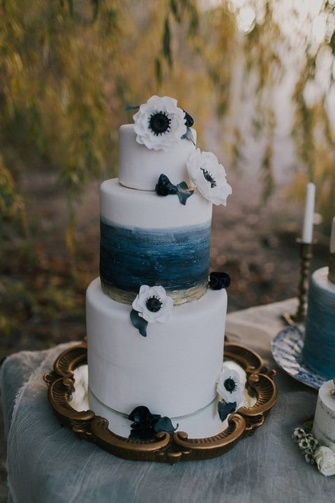 a seaside wedding cake with two white tiers and a watercolro dark blue and gold one, with white anemones