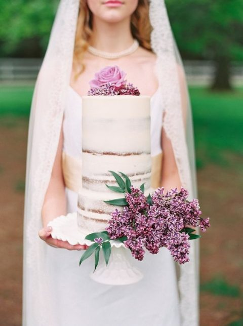 a semi-naked wedding cake topped with lilac and a rose