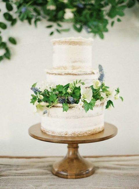 a semi-naked wedding cake with blue hyacinths, greenery and neutral blooms