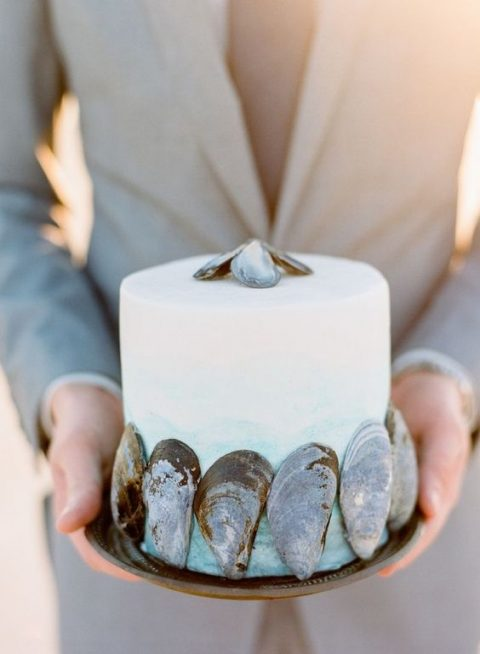 a waterclor light wedding cake with shells on the edge and on top