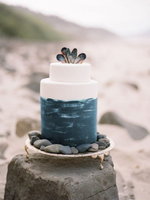 a watercolor dakr teal wedding cake with shells on to and placed on pebbles