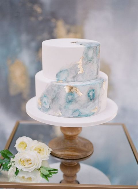 a watercolor light blue and grey wedidng cake with gold leaf
