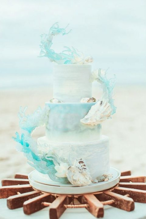 a watercolor light blue wedding cake decorated with sugar shards imitating water and shells
