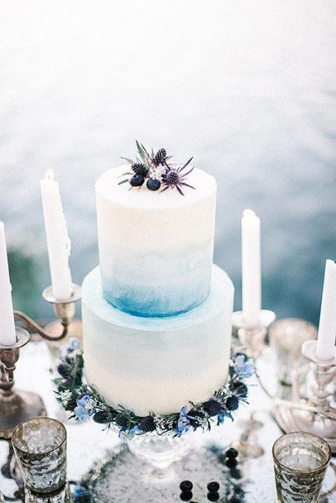 a watercolor light blue wedding cake topped with berries and thistles