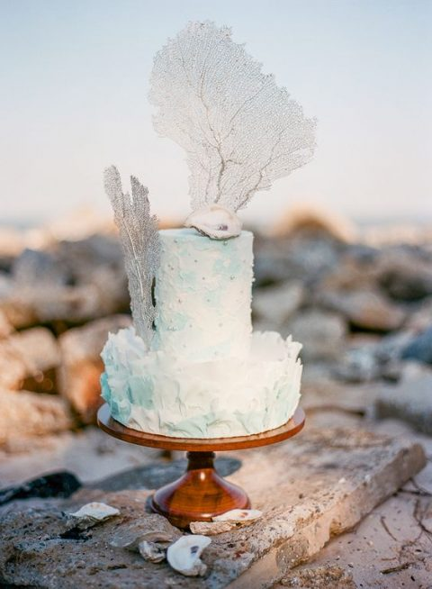 a watercolor light blue wedding cake with a texture and faux corals