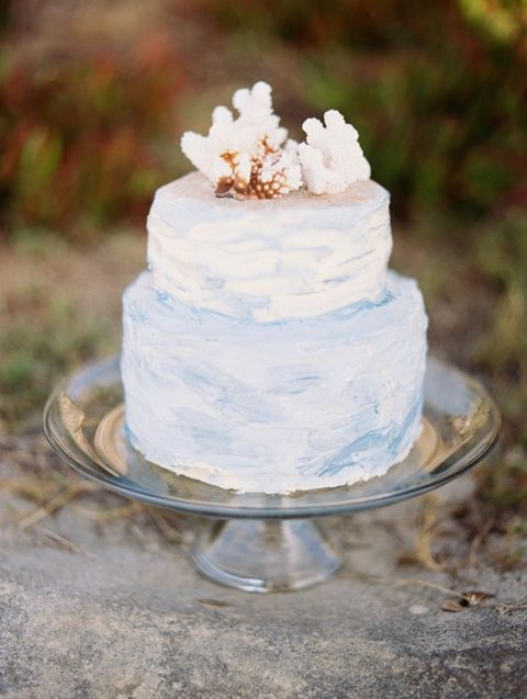 a watercolor light blue wedding cake with corals on top