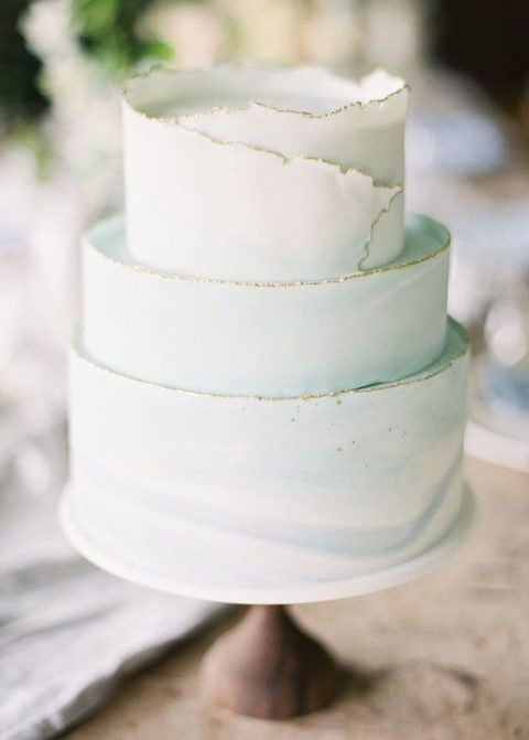 a watercolor light green-blue wedding cake with a textural gilded edge